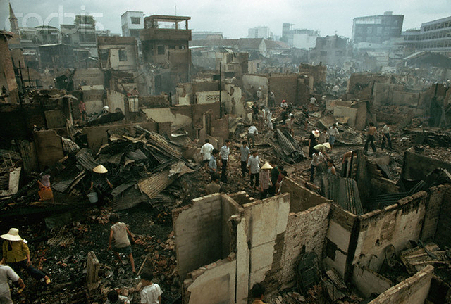 April, 28 1975, Saigon, South Vietnam --- War victims walking through rubble after buildings were hit by a Vietcong missile in Saigon, South Vietnam. --- Image by © Nik Wheeler/CORBIS
